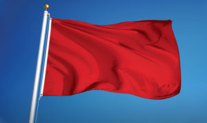 A rectangular red flag blowing in the wind against a crisp blue background. The red flag is attached to a white pole that has a brass ball on the top.