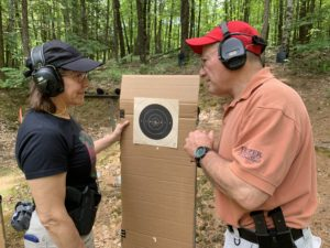 Firearms expert George Harris stands beside a target at an outdoor range with his student, Beth Grote (Linda Harris Memorial Scholarship Winner)