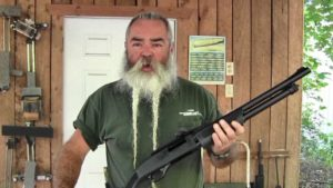 Jeff Quinn of the Gunblast YouTube channel. He has two long braids in his white beard and is holding a shotgun in his left hand.