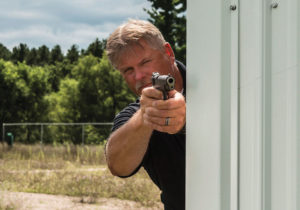 A man with gray hair and mustache takes aim with a 1911-style semi-automatic pistol from around the edge of a building.