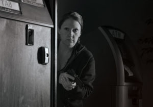 A woman hides behind a snack machine with her pistol at the ready. She peers around the edge of the machine.
