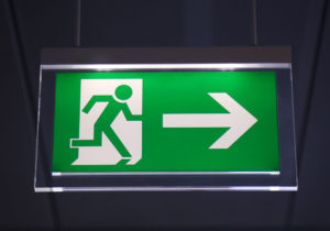 A green EXIT sign depicting a stick figure running in the direction indicated by a big arrow.