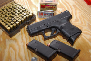 A black Glock 26 concealed-carry pistol lying beside two loaded magazines and a tray of 9mm ammunition.