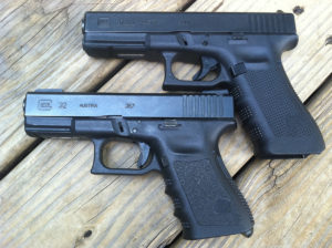 Two black Glock pistols, a Glock 17 in 9mm and a Glock 32 chambered in .357 SIG, lying on an untreated wooden deck