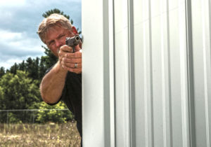 A man peers out from behind a sheet metal wall with a black pistol held in both hands