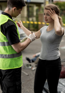 A young woman in a gray T-shirt and black pants holds her head with her left hand and motions with her right while providing a statement to an emergency worker wearing a neon green safety vest. He is taking notes with a pen held in his gloved right hand. Police caution tape is strung across the background.