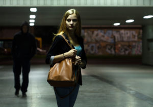A young woman clutches the shoulder strap of a large brown purse as she walks alone through an empty parking structure. A figure dressed all in black is emerging from the shadows behind her field of vision.