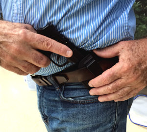 A white senior citizen with liver-spotted hands cross-draws a small black pistol out of an IWB holster at his waist.