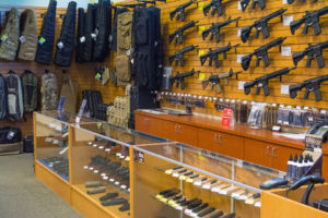 Your typical gun store sales counter featuring handguns in a glass cabinet and an array of long guns on a peg board rack along the back wall. An adjacent wall holds a display of rifle cases in various tactical colors.