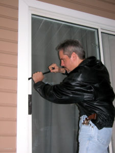 A white man with salt-and-pepper hair, wearing a black leather jacket and blue jeans, uses a crowbar to pry open a residential patio door. The man has a bright silver revolver with wooden grips tucked into his left hip pocket as he breaks in.