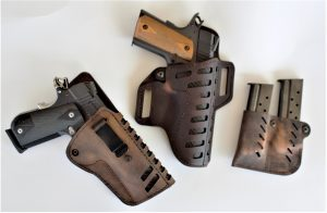 Two andguns tucked into leather Versacarry brand leather holsters and a pair of steel magazines inserted into a leather Versacarry magazine pouch, set against a white background