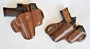Two black handguns tucked into brown leather DM Bullard holsters set against a white background.