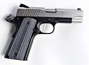 A two-tone 9mm Ruger SR1911 Commander pistol with the hammer cocked back, lying on a white background