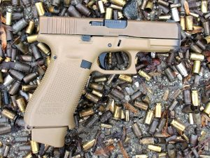 A FDE Glock 19X 9mm pistol lying on the ground amid a large quantity of old spent brass at an outdoor pistol range.