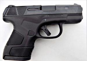 A black Mossberg MC1 pistol lying on a white tabletop.