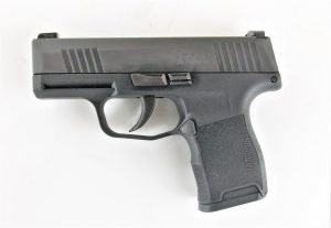 A SIG Sauer P365 comcealed carry andgun lying on a white background.