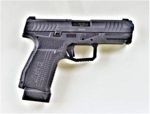 An AREX Rex Delta 9mm handgun lying on a white background.