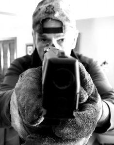 A blac-and-white photo of a man wearing a backwards baseball cap aiming a handgun at the camera.
