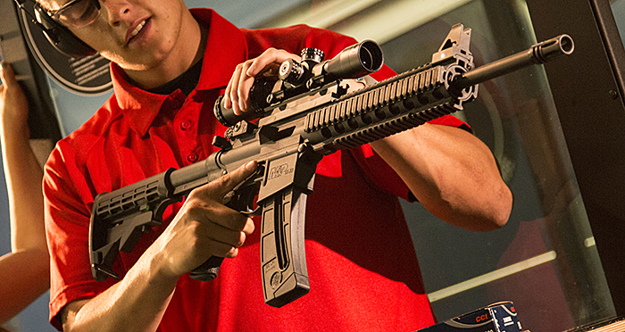 A man in a red polo shirt inspects an AR-15 rifle fitted with an optical scope. He is practicing proper trigger finger discipline and has the muzzle pointed downrange at an indoor range.