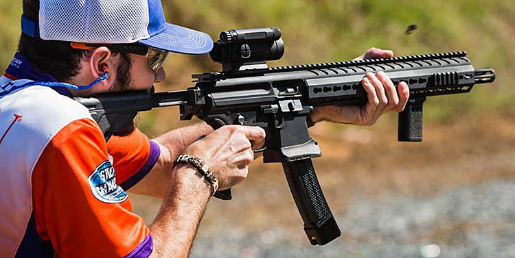 A man fires a 9mm carbine during a shooting competition on an outdoor range